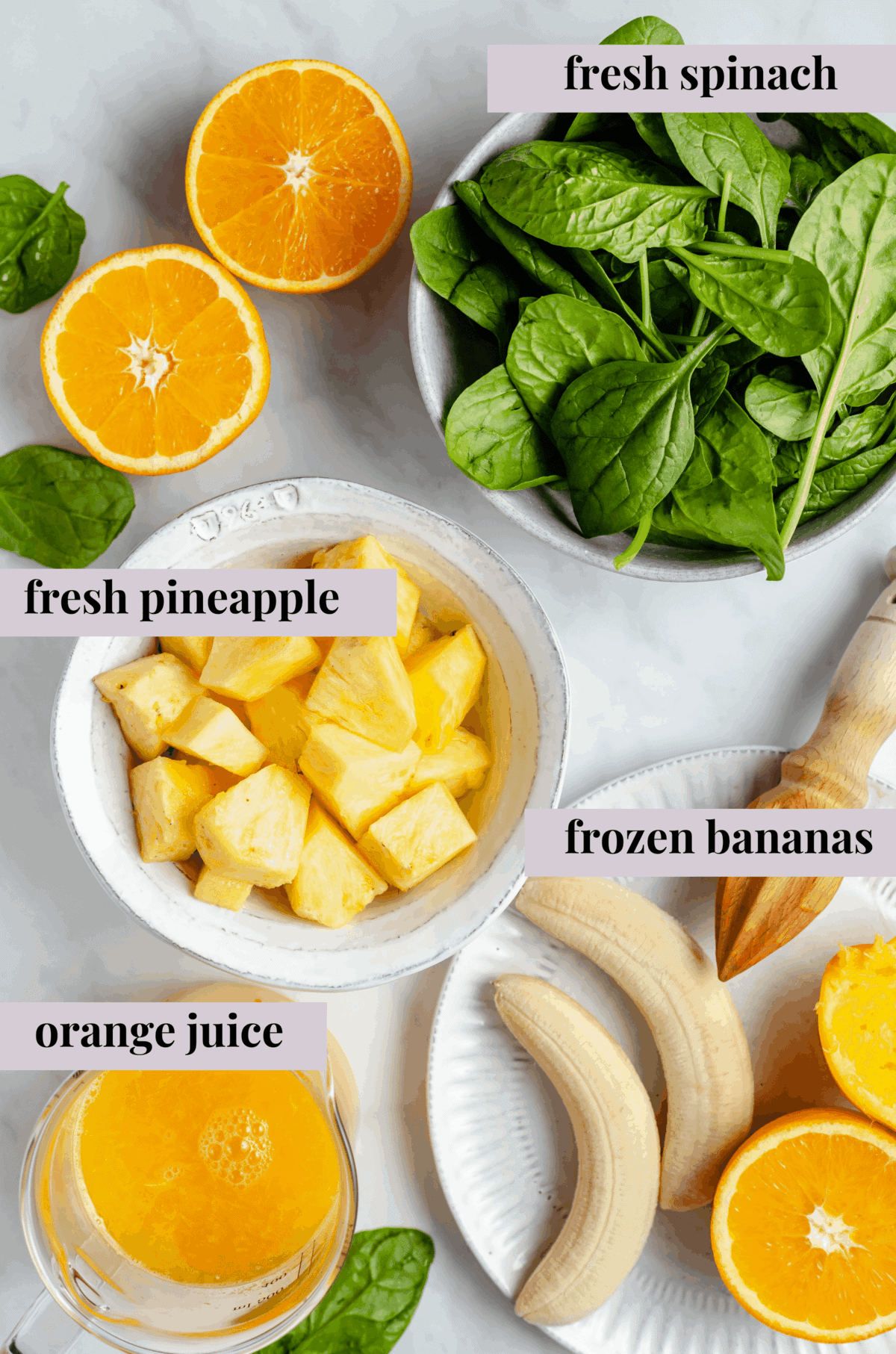 labeled ingredients of smoothie on a white counter
