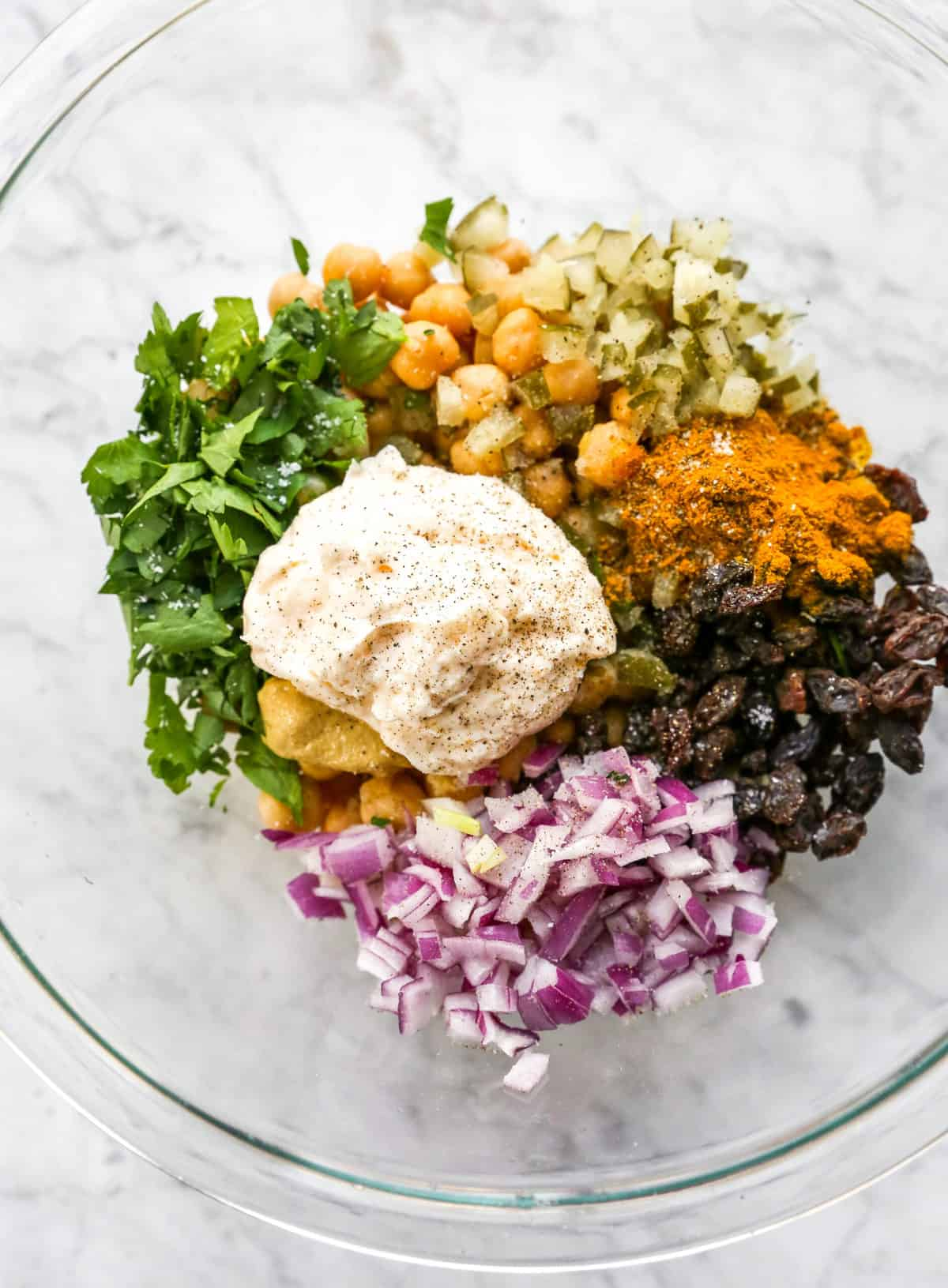 curried chickpea salad ingredients in a bowl before mixing