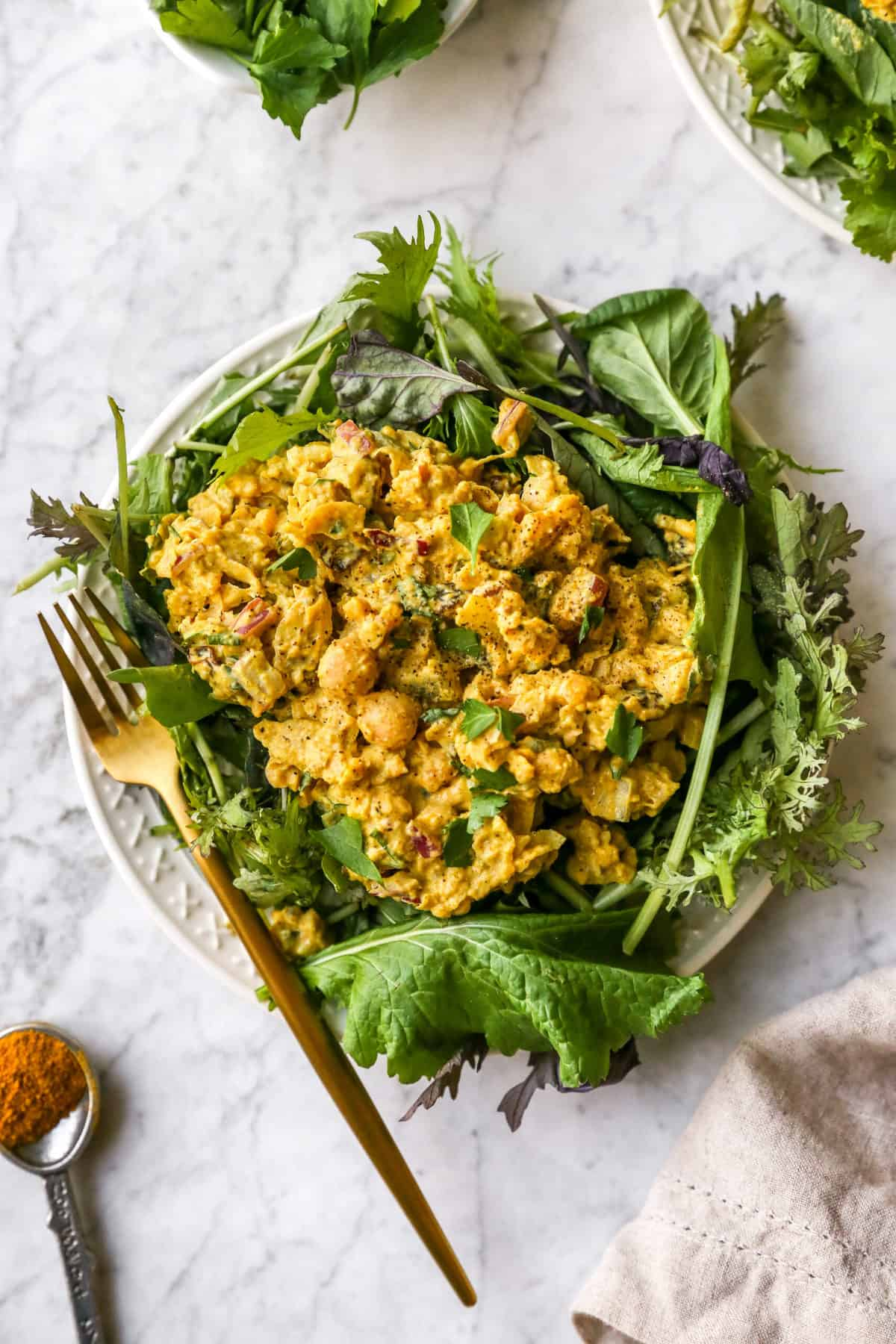 curried chickpea salad on a bed of greens
