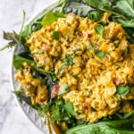 close up shot of curried chickpea salad on a bed of greens