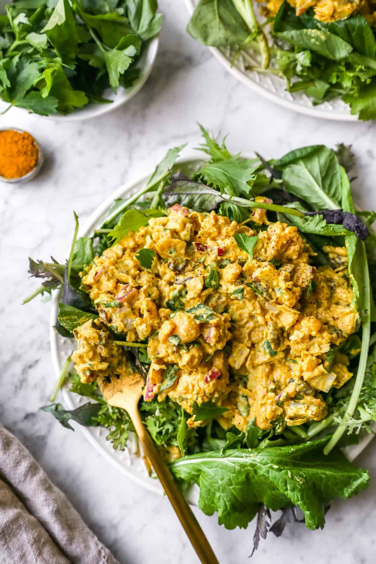 curried chickpea salad on a plate with other plates in the background