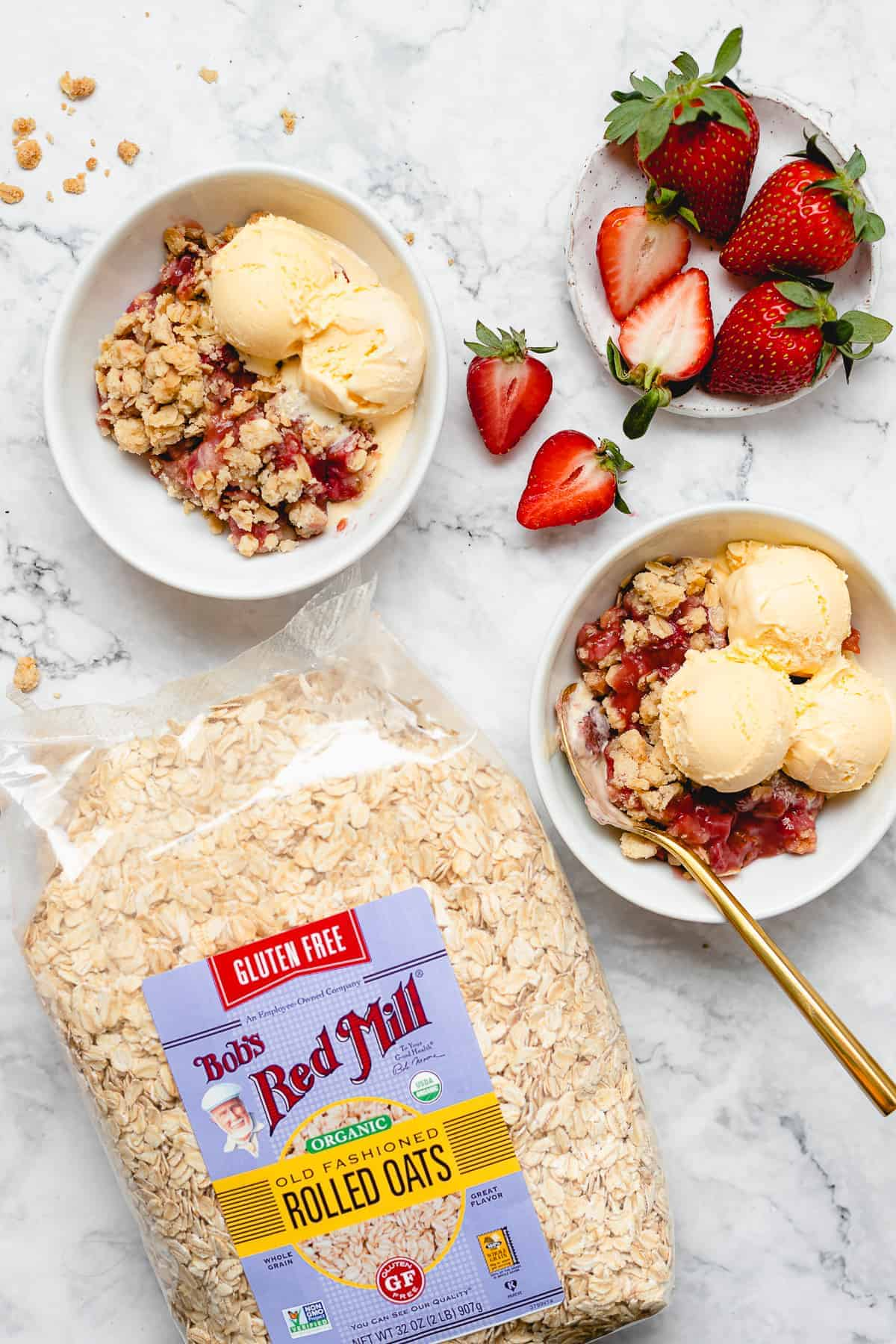 vegan strawberry crisp in two bowls with a bag of oats