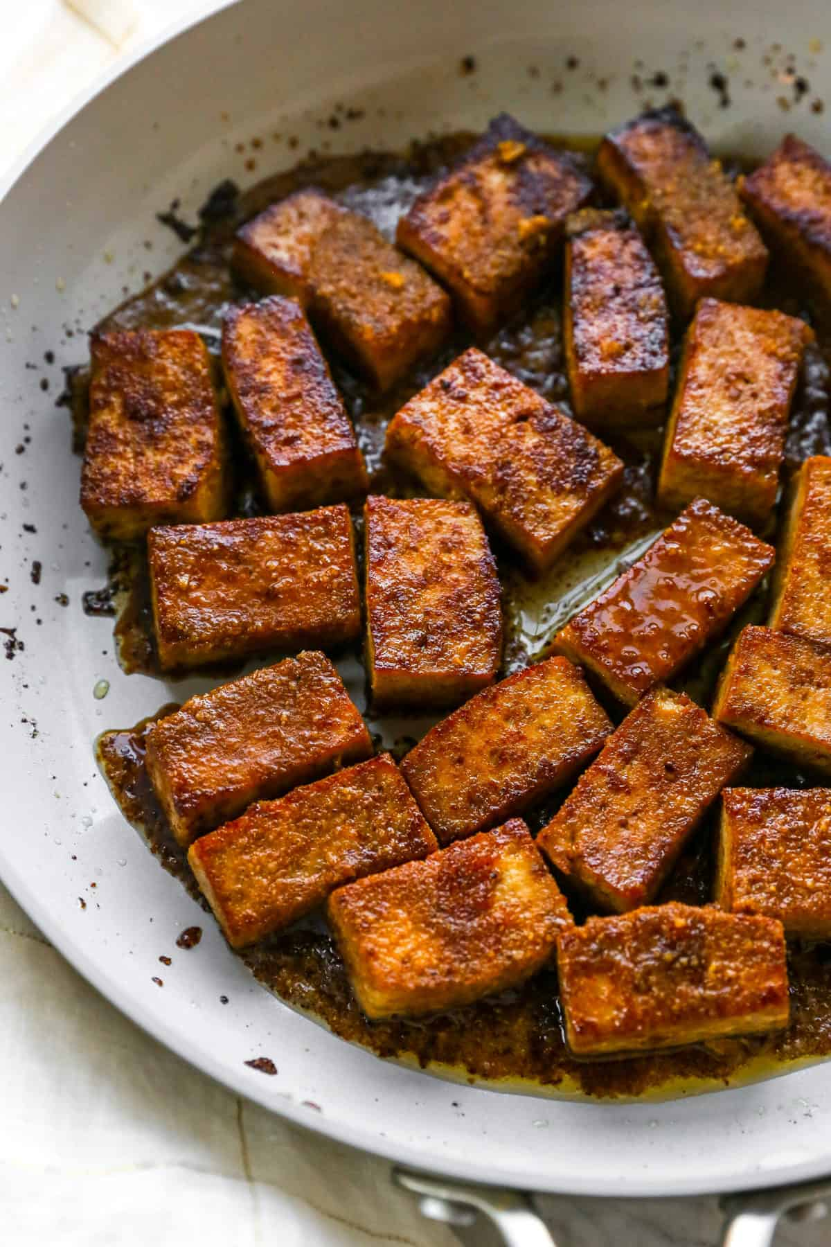 marinated and cooked tofu with leftover sauce in pan