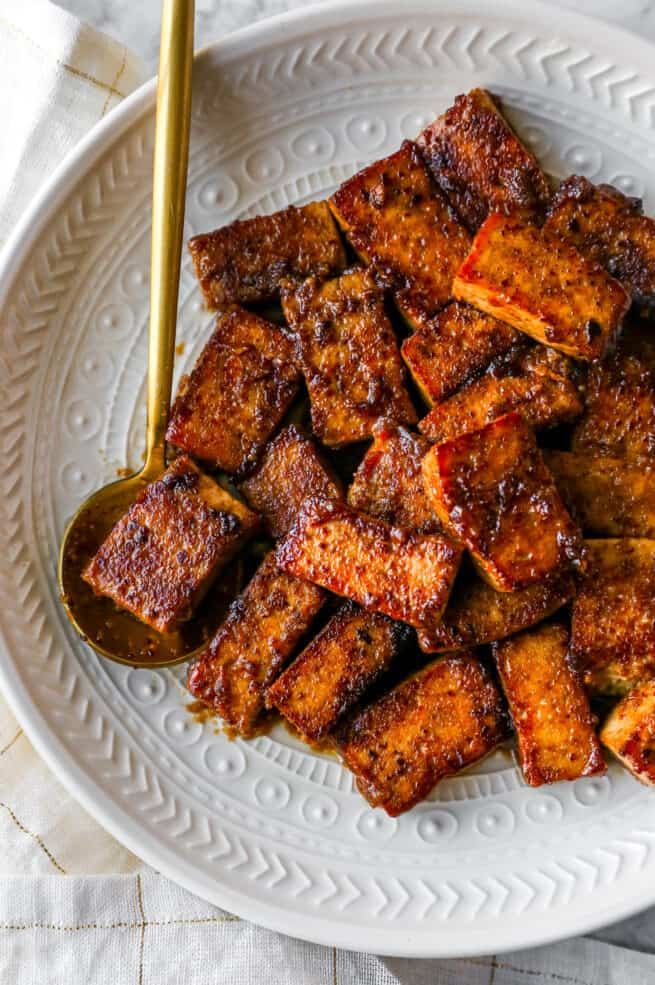 marinated and cooked tofu on a plate with a gold spoon holding some tofu