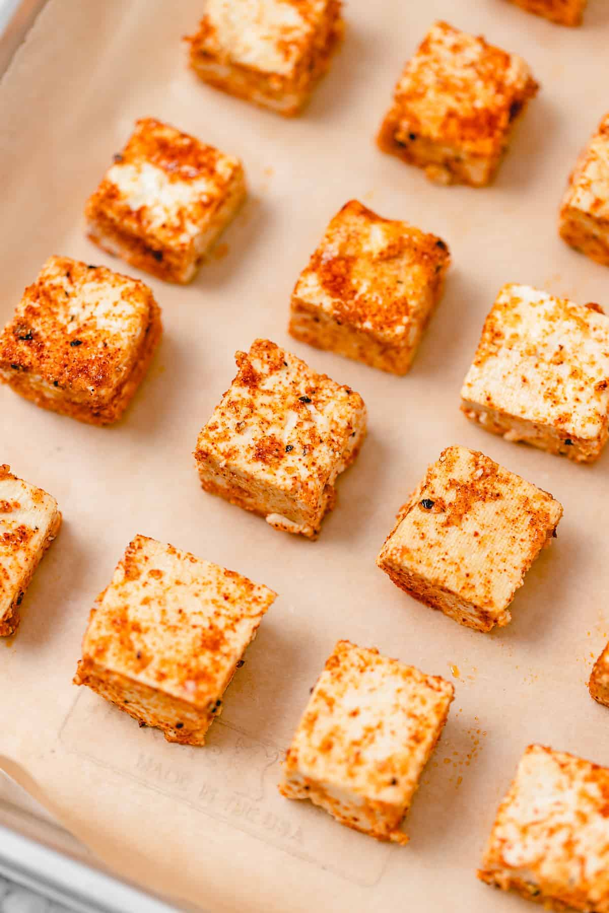 Cubes of uncooked firm tofu covered in seasoning on parchment paper