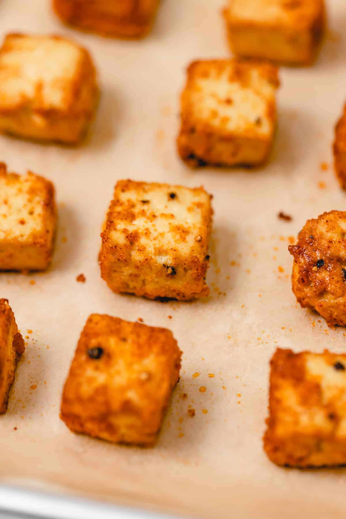 Baked tofu on a baking sheet with parchment paper dusted in black pepper, paprika, and other seasonings