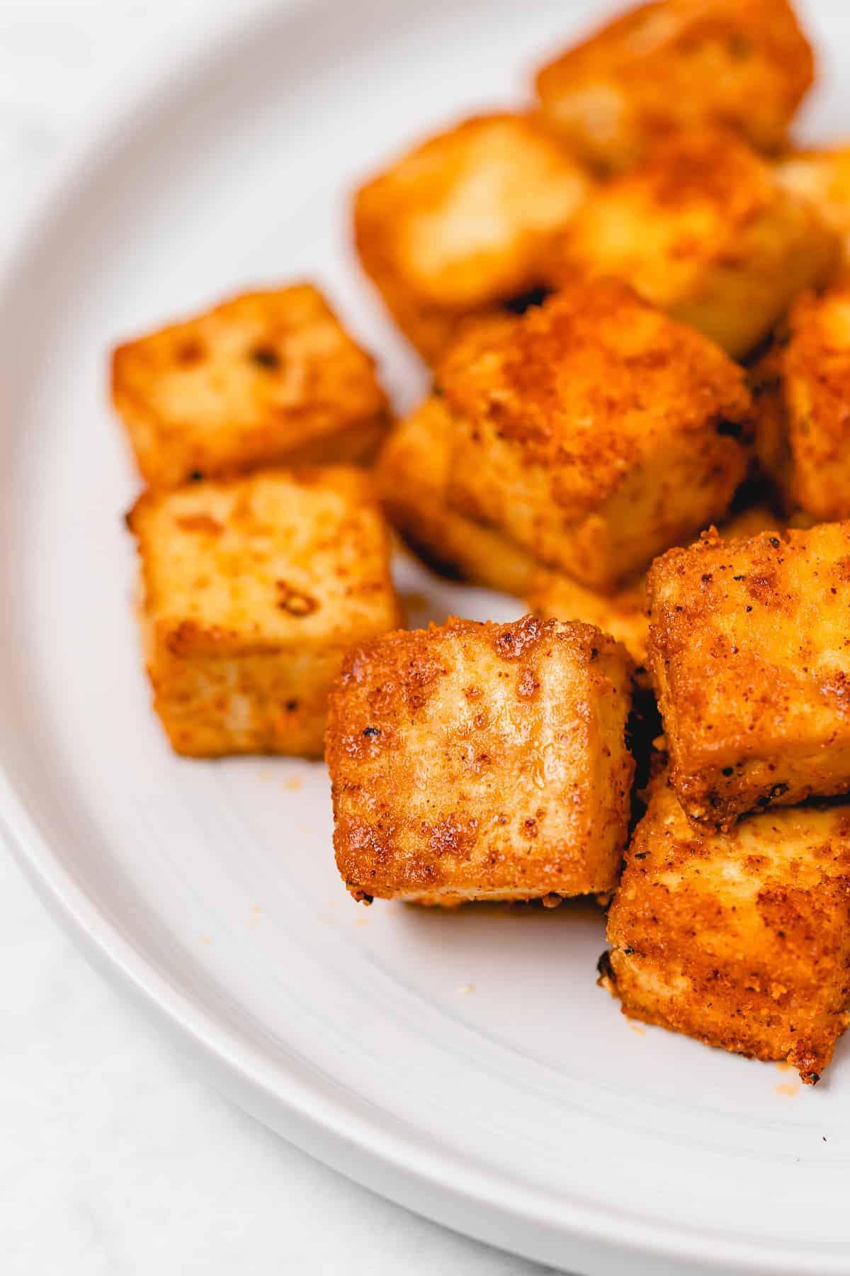 Close-up shot of crispy tofu cubes on a white ceramic plate