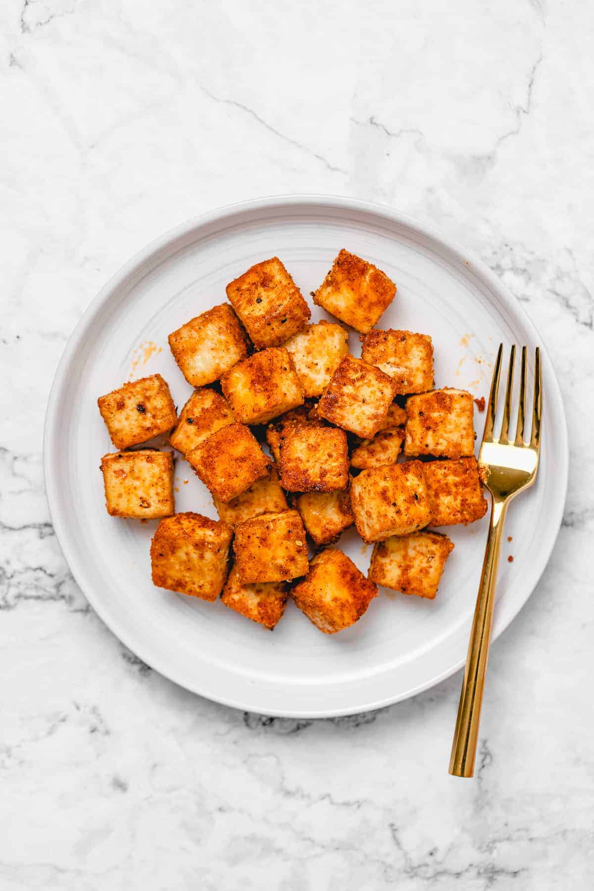 Crispy baked tofu on a white round plate with a gold fork