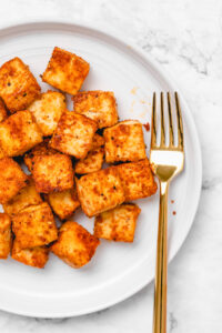 Close-up shot of crispy seasoned tofu on a round white plate with a gold fork