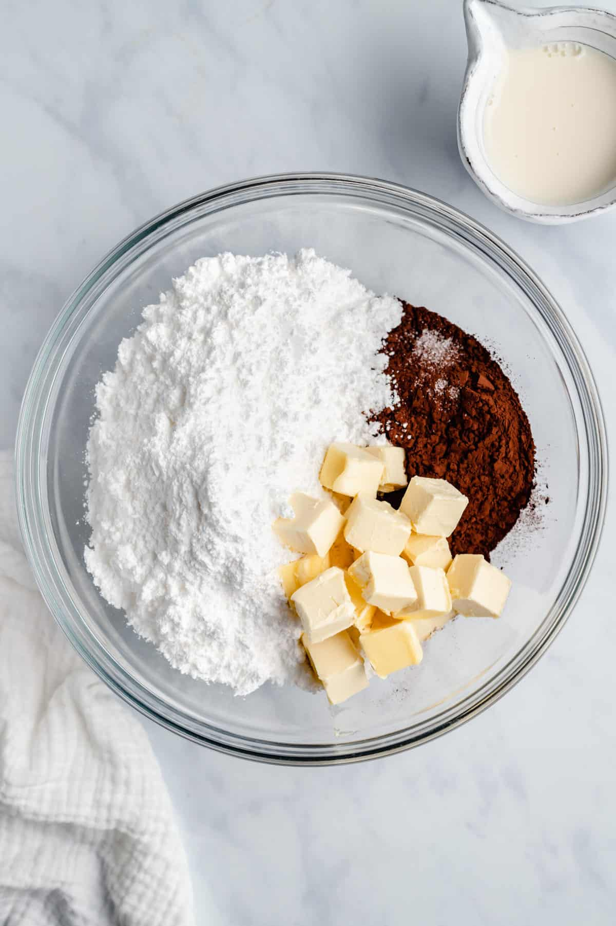 Powdered sugar, butter, and cocoa powder in a glass mixing bowl