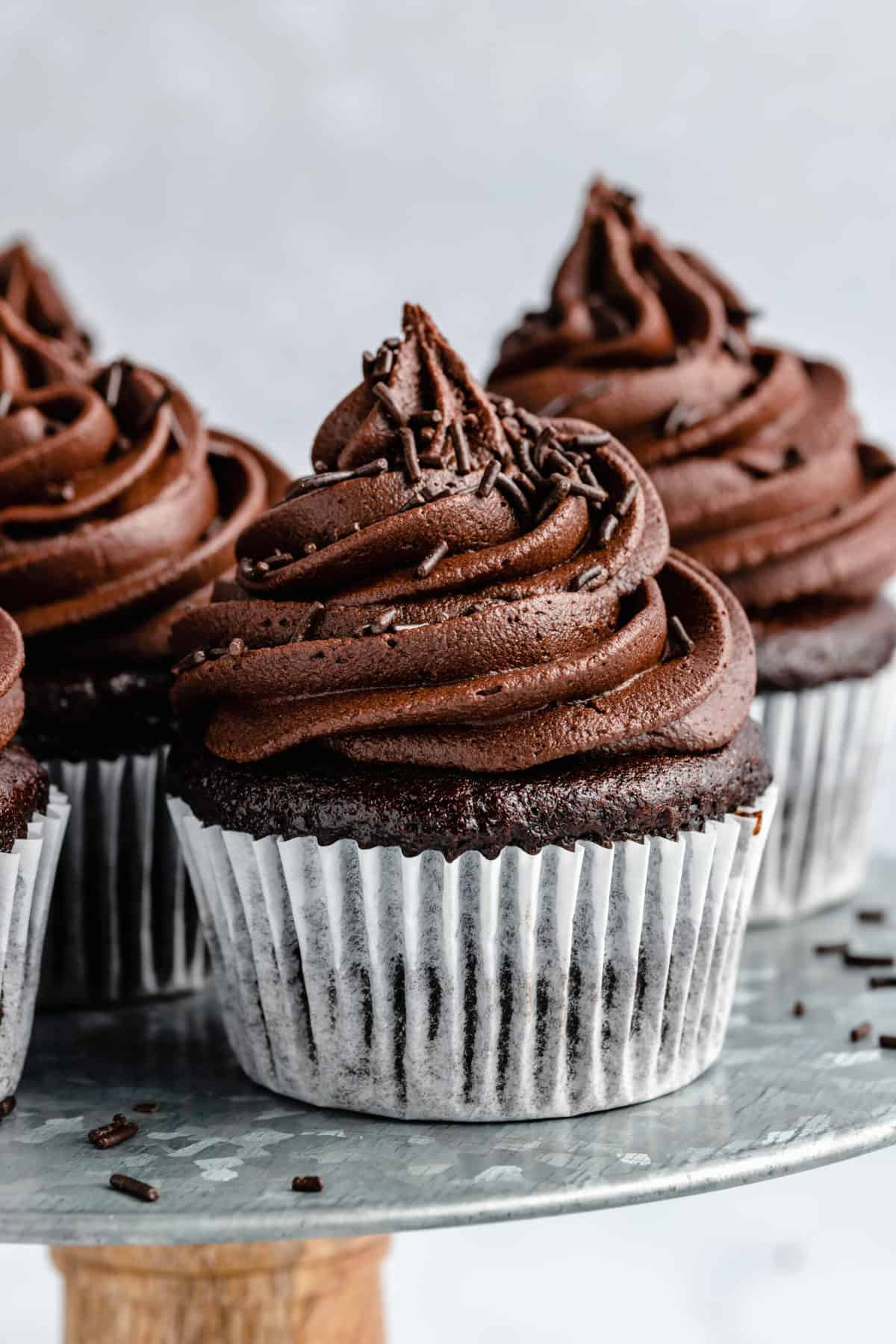 Chocolate cupcakes topped with vegan chocolate frosting in white cupcake papers