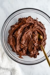 Glass mixing bowl of rich chocolate frosting with a gold spoon