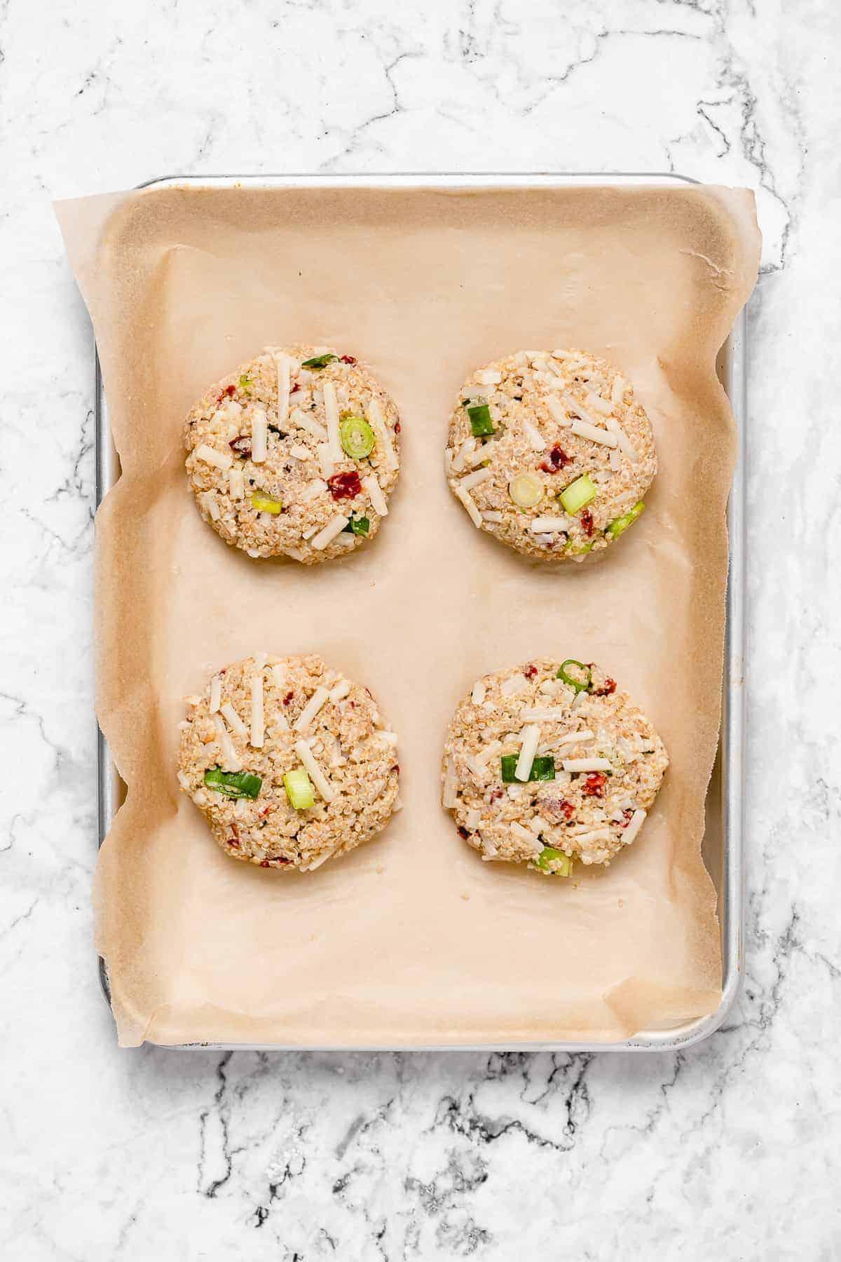 Four quinoa veggie burger patties on a baking sheet with parchment paper