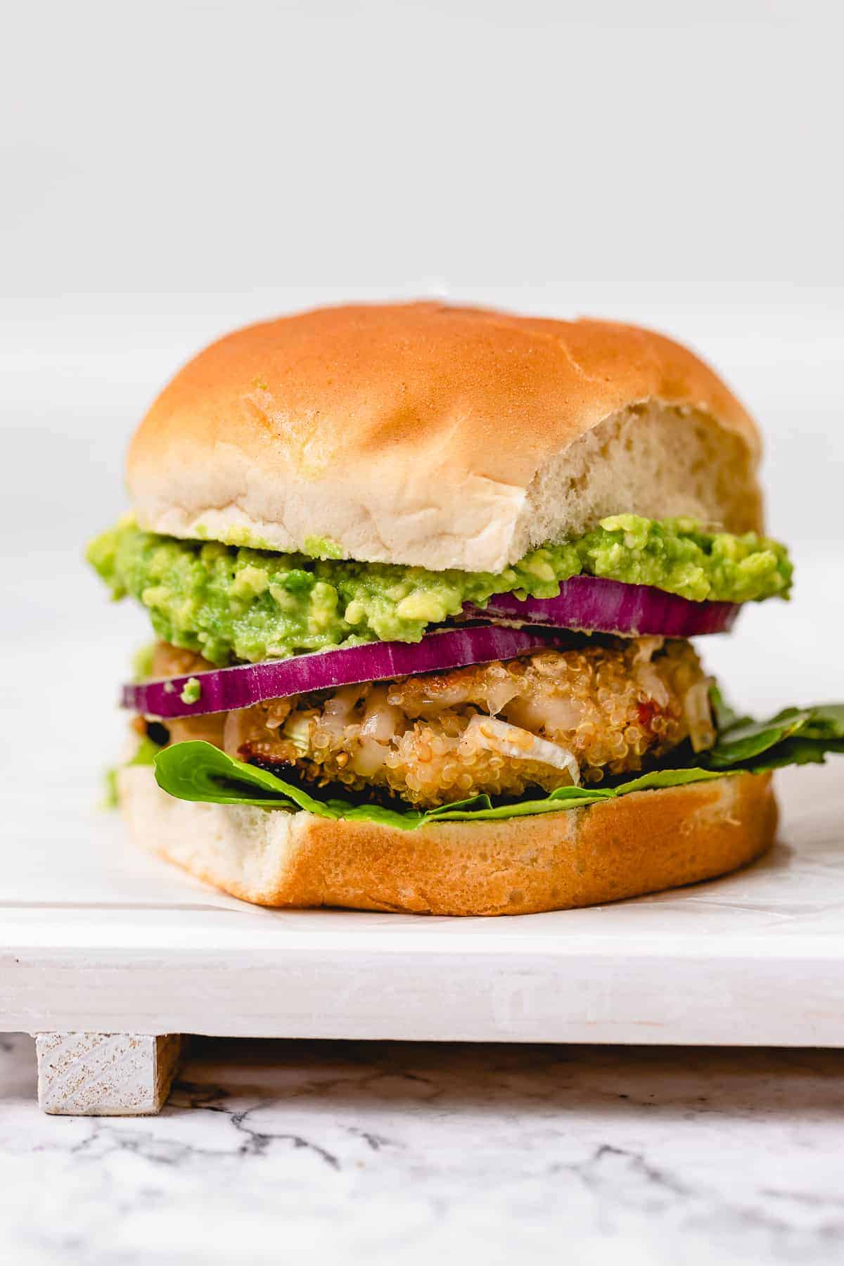 Quinoa veggie burger with lettuce, red onion, and avocado on a white bun on a board