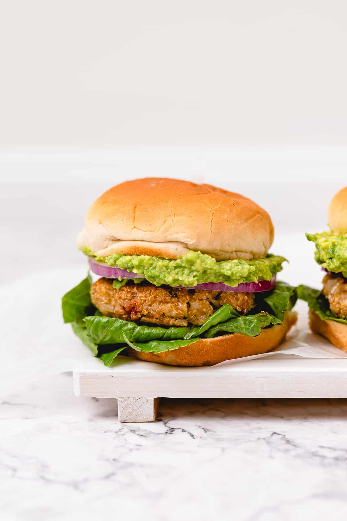 Two golden brown veggie burgers with avocado, red onion, and lettuce on fluffy vegan buns