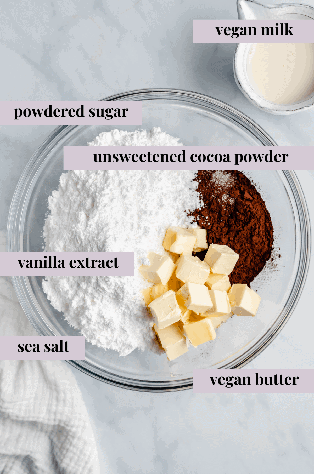 powdered sugar, cocoa powder, vanilla extract, salt, and vegan butter in a glass bowl