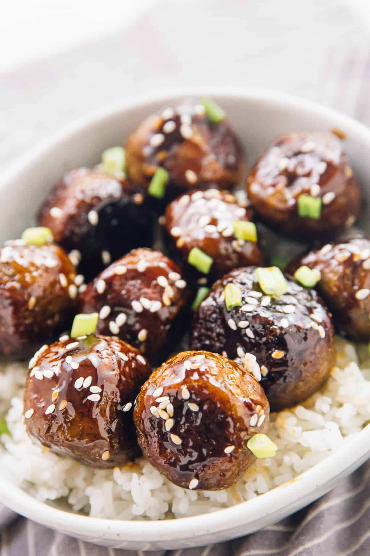 Close-up shot of veggie meatballs covered in sauce on a bed of white rice