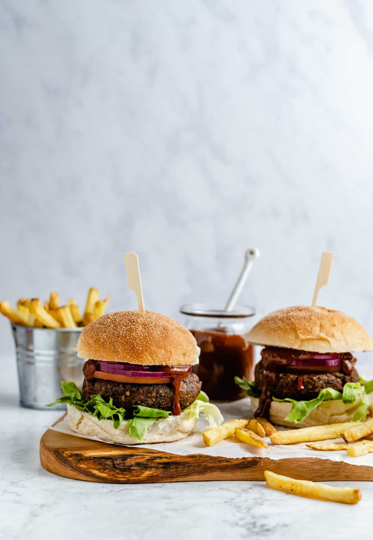 Two black bean burgers with strawberry BBQ sauce.