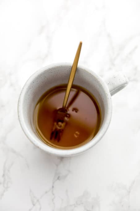 Vanilla extract, oil, and lemon juice in a mug.