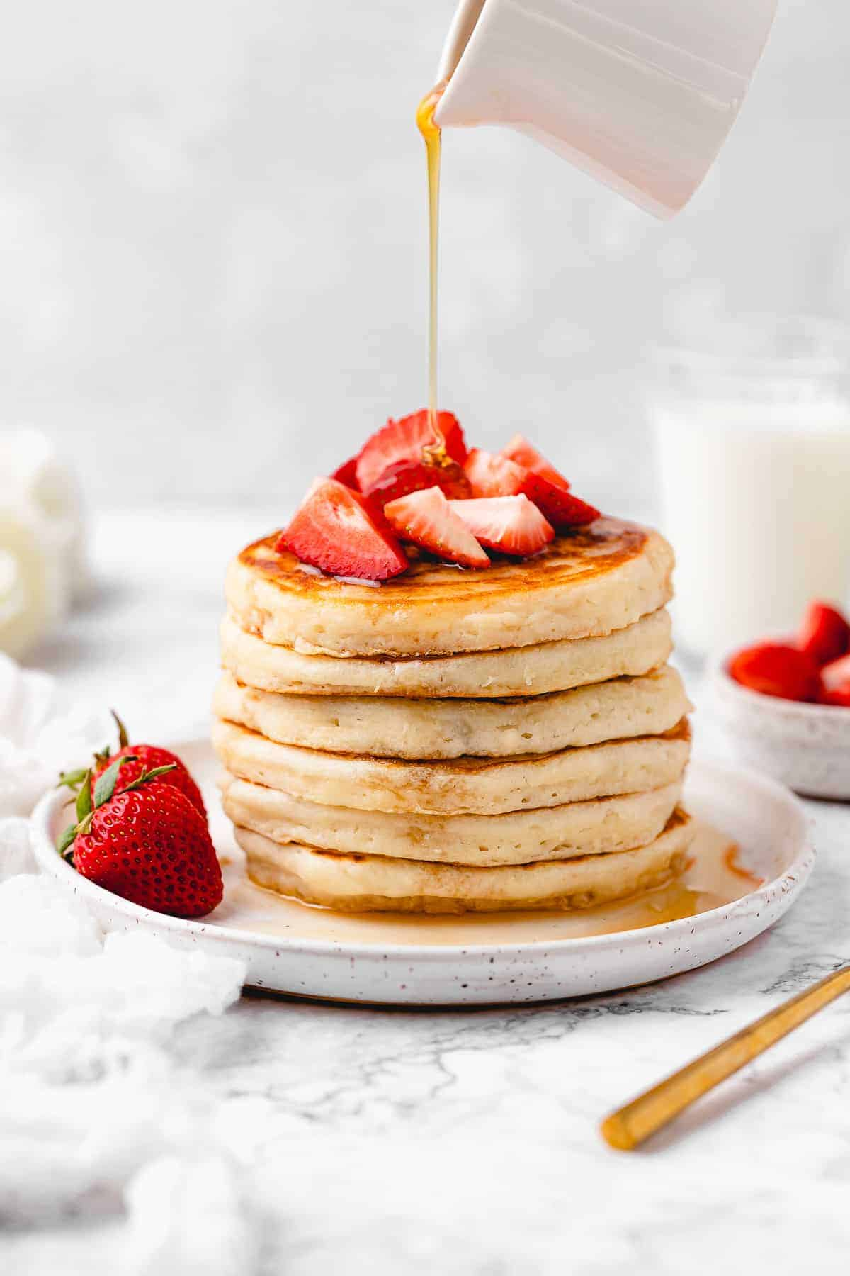 Stack of pancakes topped with strawberries.
