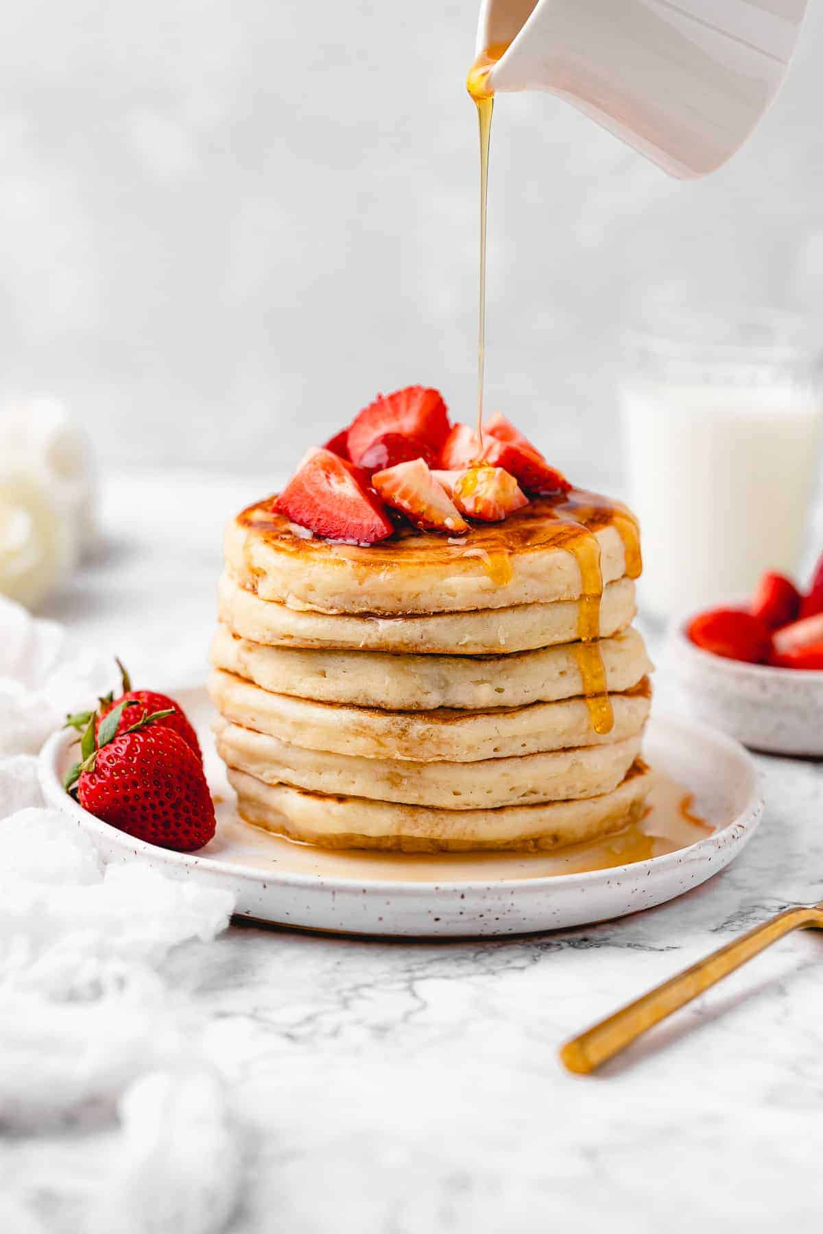 Pancakes topped with strawberry and maple syrup.