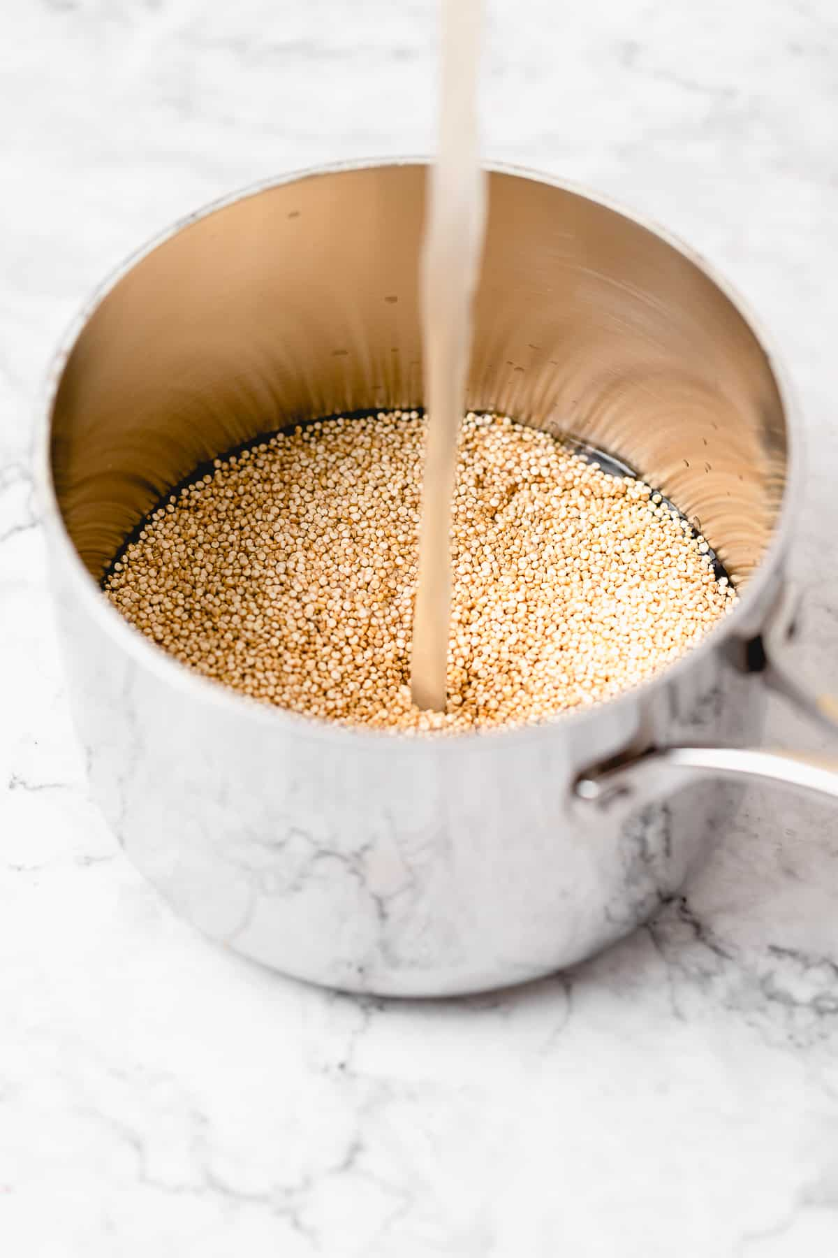 dry quinoa in a measuring cup with veggie broth being poured in