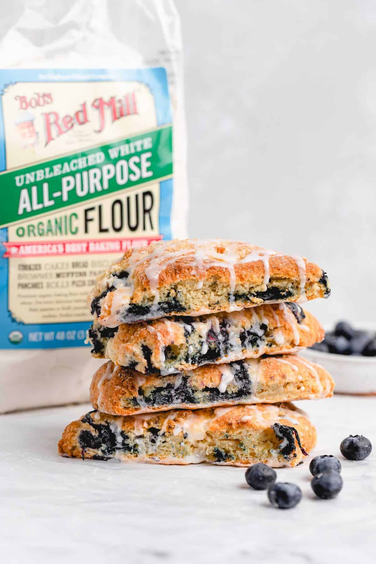 four stacked blueberry scones with a bag of Bob's Red Mill flour behind it
