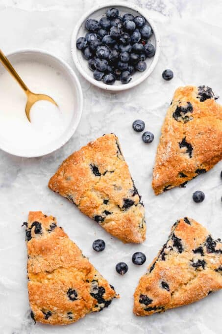 baked blueberry scones with a bowl of lemon glaze and blueberries
