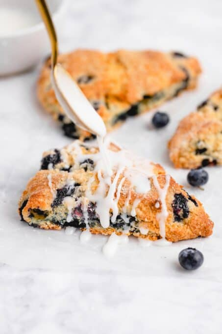 white glaze being drizzled onto a blueberry scone