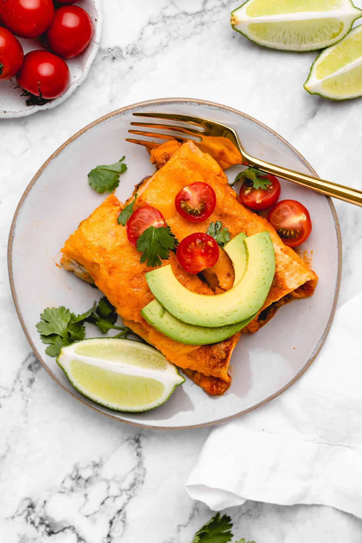 Plate of vegan enchiladas with avocado slices.