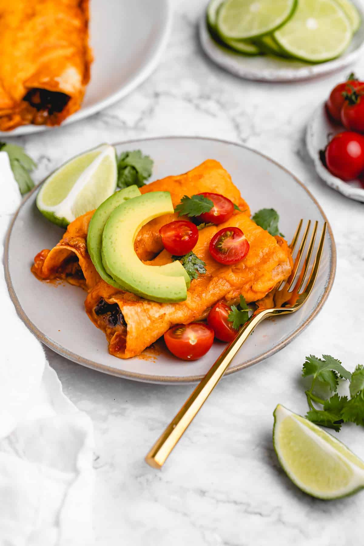 Plate of cheesy enchiladas with a wedge of lime.