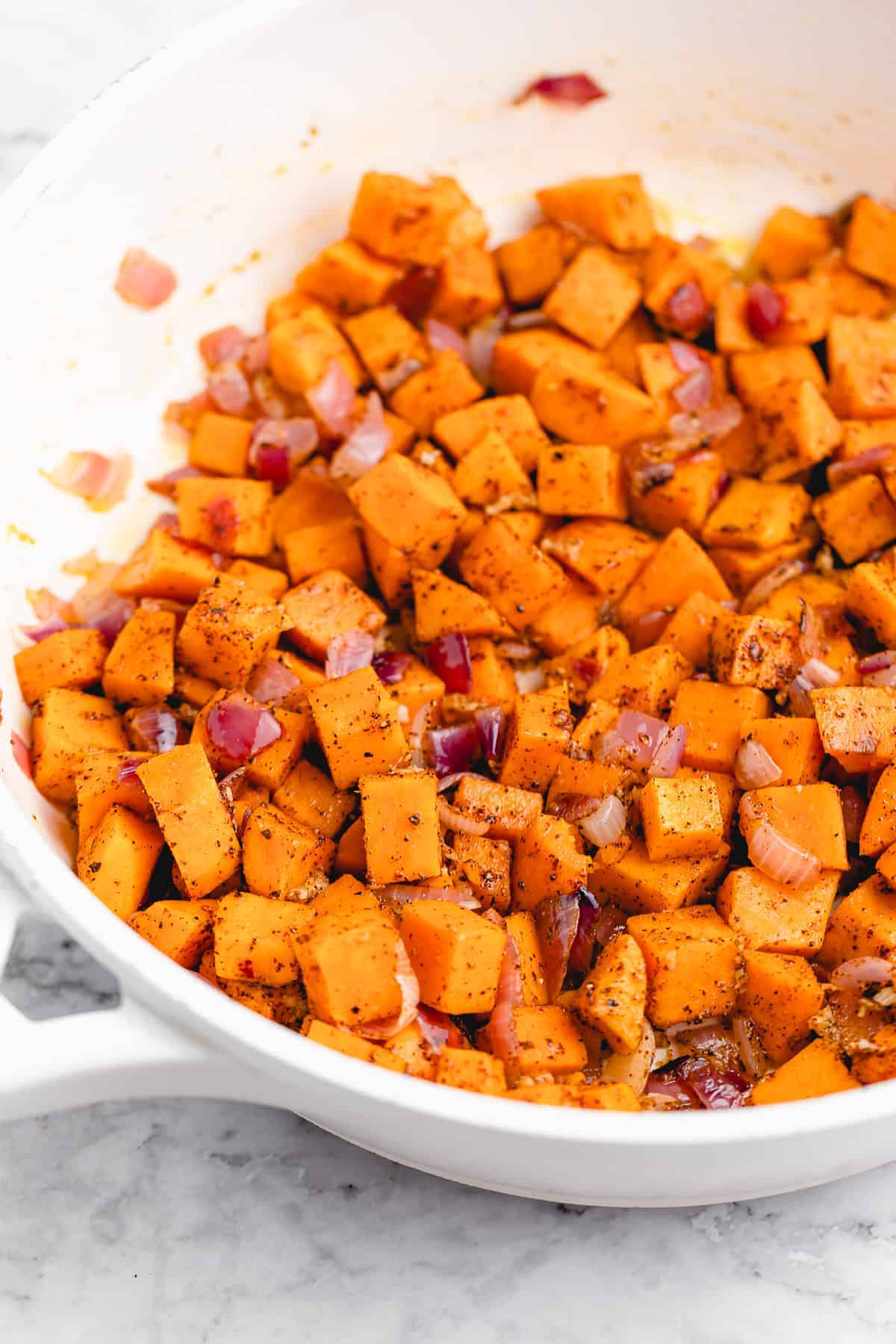Pan of sautéed red onion and sweet potatoes.
