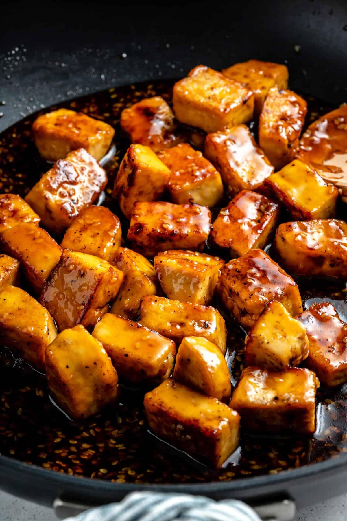 Teriyaki tofu cooking in a frying pan.