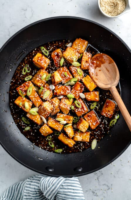 Tofu cooking with chopped scallions.