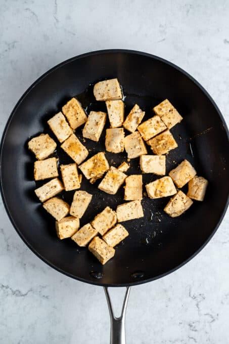 Tofu cubes in a frying pan.