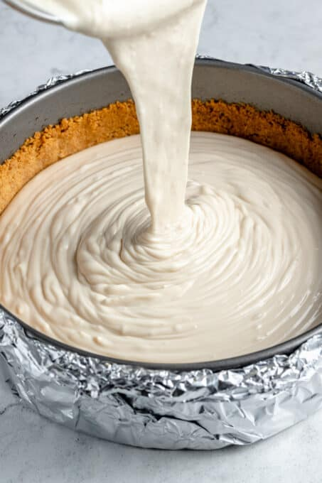 Vanilla cheesecake filling being poured over graham cracker crust.