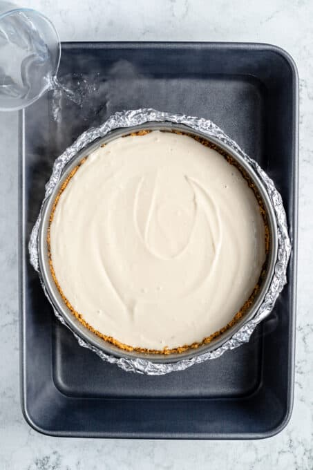 Unbaked vanilla cheesecake in a springform pan.
