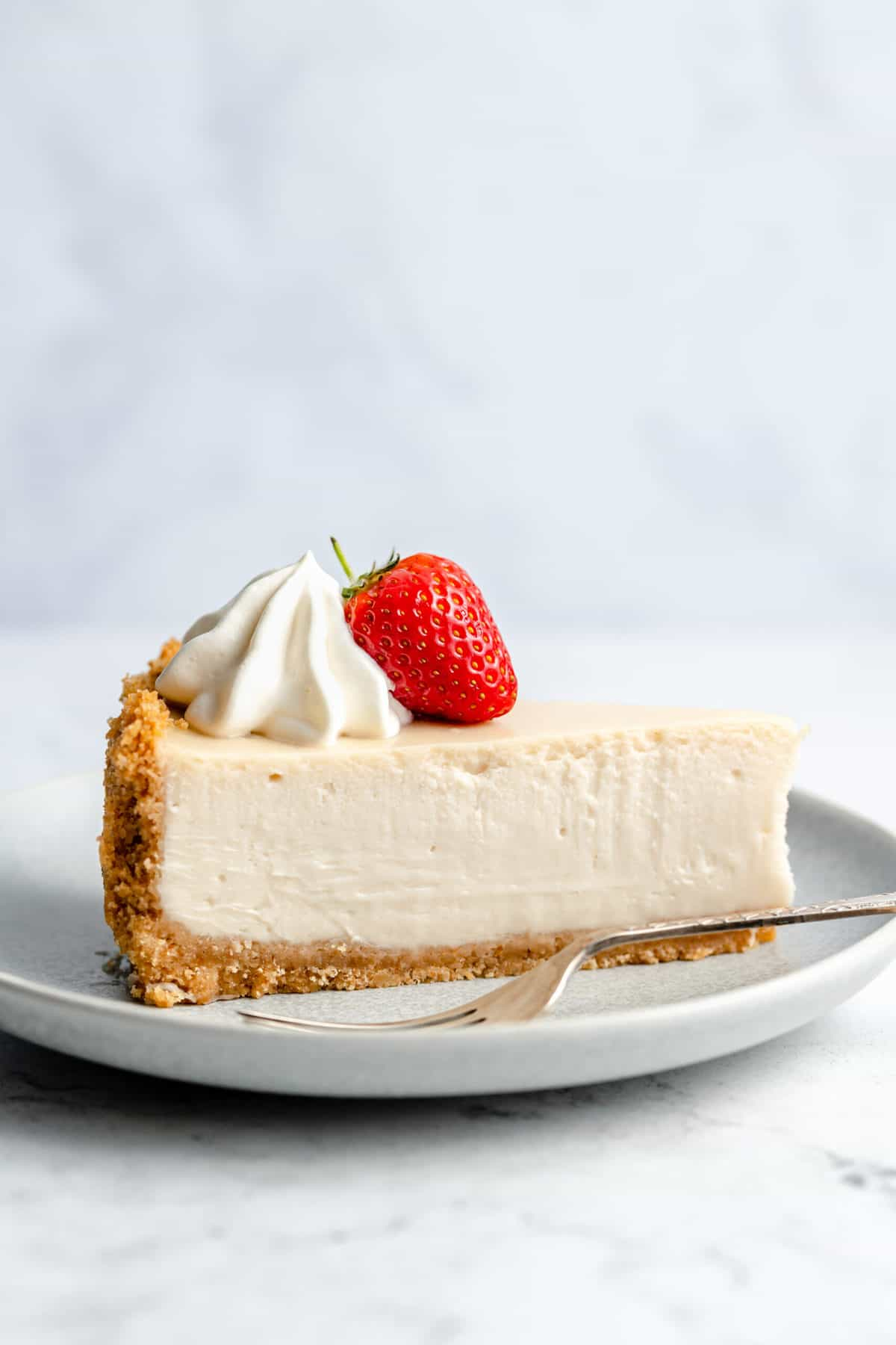Slice of vanilla cheesecake with a strawberry.