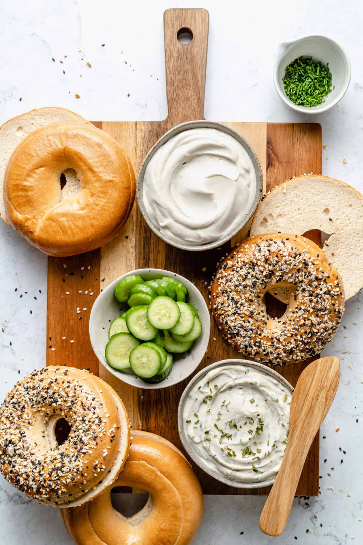 Bagels with cream cheese and cucumber slices.