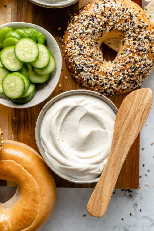 Plain cream cheese with bagels on a cutting board.