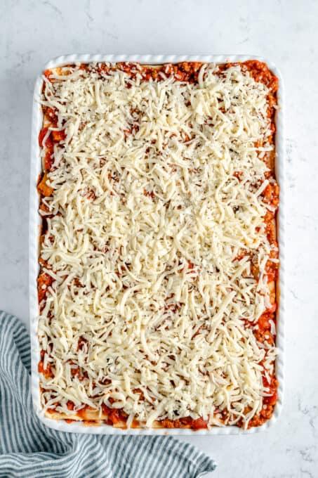 More shredded vegan mozzarella on top of the lasagna.