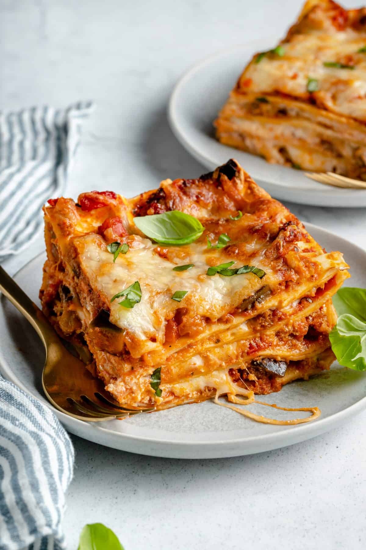 A plate of cheesy lasagna with basil.