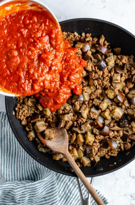 Tomato sauce poured into a pan of vegan meat and eggplant.