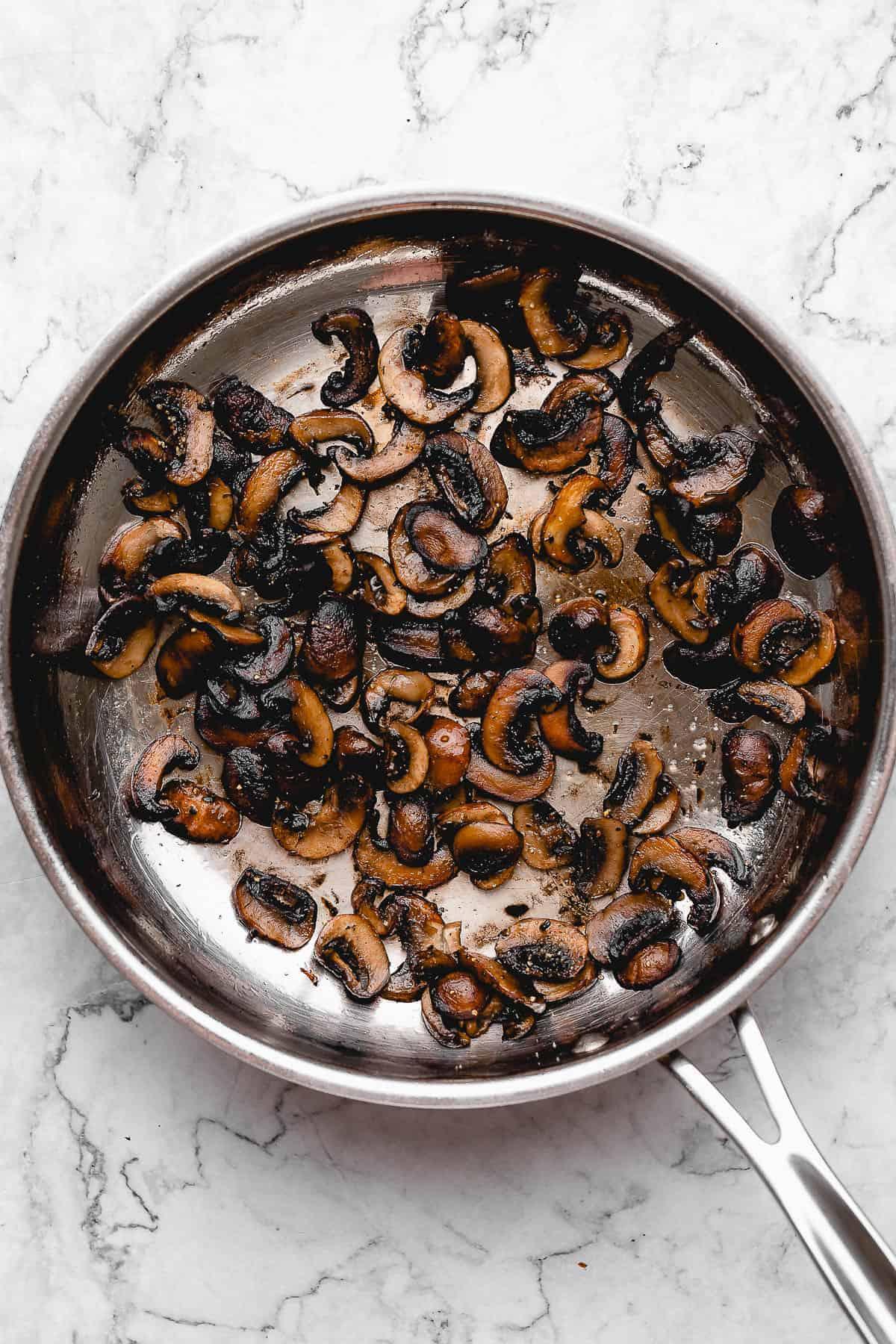 Sautéed mushroom slices in a pan.