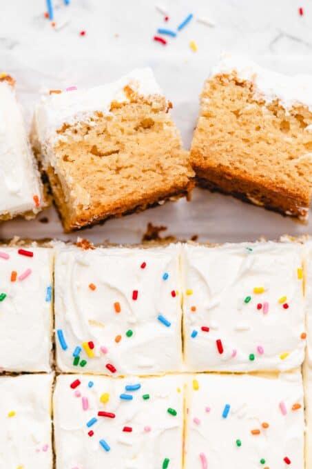 Squares of vegan vanilla sheet cake with frosting.
