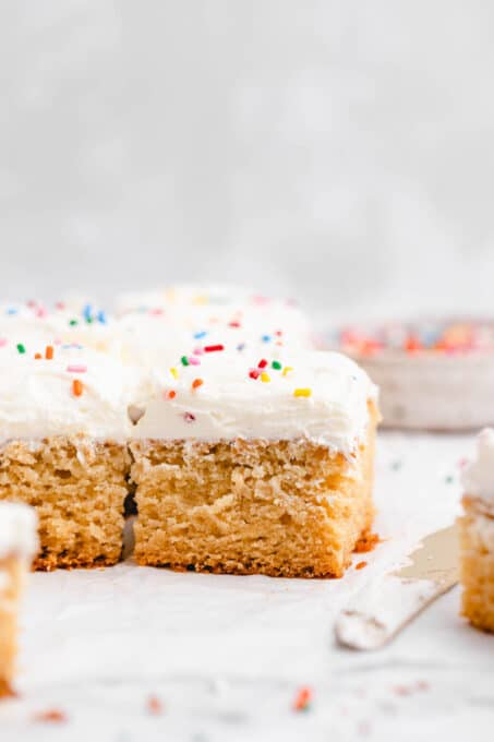 Squares of vegan cake with vanilla buttercream frosting.
