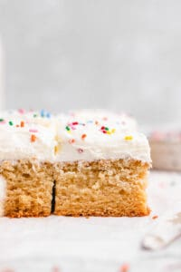 Frosted cake squares with rainbow sprinkles.