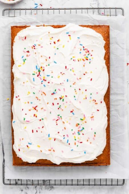 Buttercream frosting with sprinkles on vanilla sheet cake.