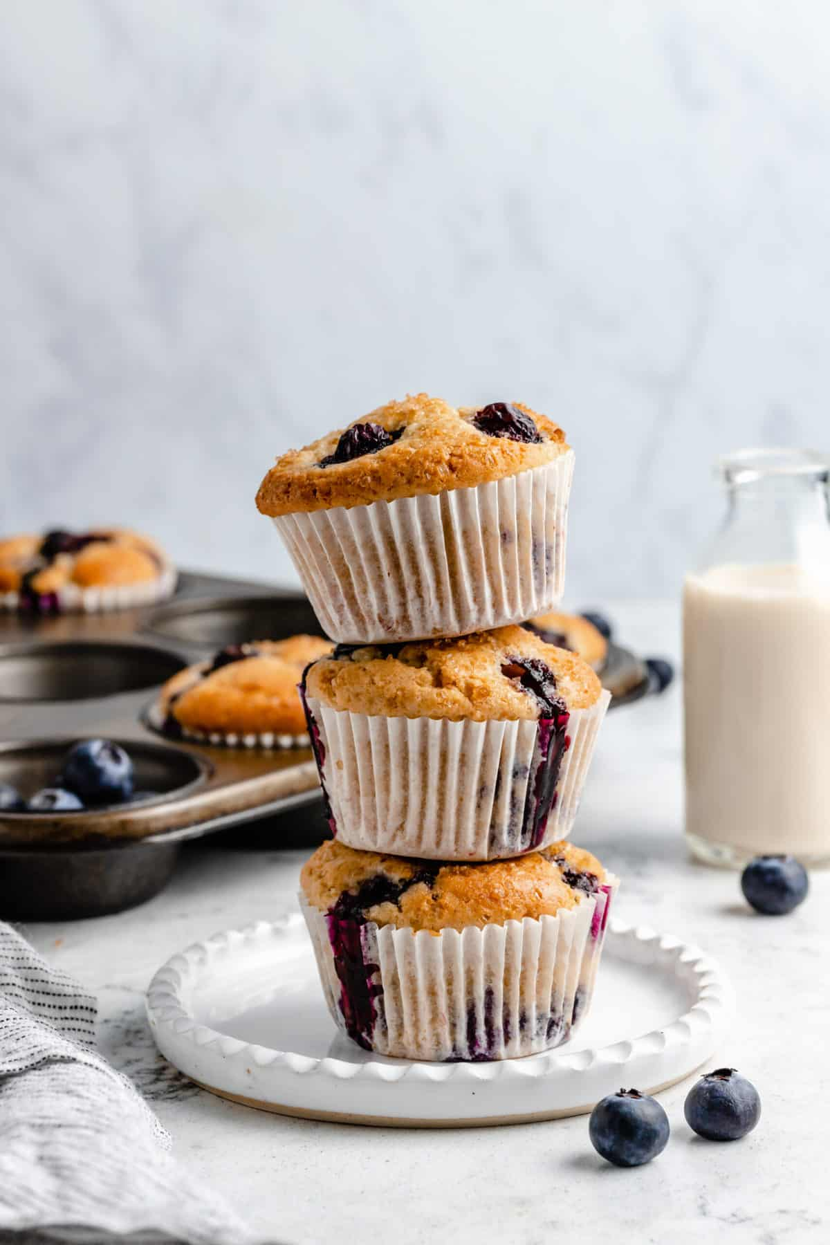 Three stacked blueberry muffins on a plate.