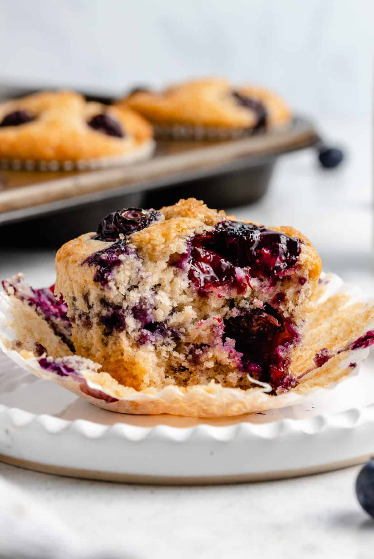 Blueberry muffin with a bite taken out of it.